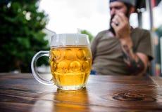 Koppla av med en drink i den bekväma stången Förnyande drink på kafétabellen Hipster som tycker om öldrinken i bar fotografering för bildbyråer
