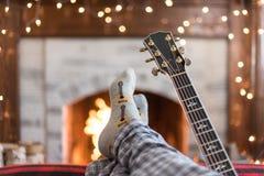 Koppla av med fot upp framme av branden med den akustiska gitarren Royaltyfria Bilder