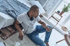 Koppla av med musik Bästa sikt av den stiliga unga afrikanska manchooen Royaltyfri Foto