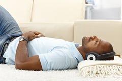 Koppla av med musik på hörlurar Arkivbild
