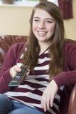Koppla av och hållande ögonen på TV för tonårs- flicka hemma Arkivbilder