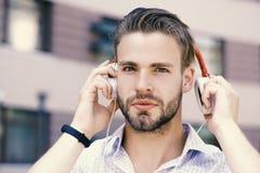 Koppla av och musikbegreppet Dj-musiksång Lyssnande musik för ung man med hörlurar på stads- bakgrund Royaltyfri Foto