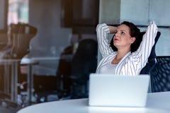 Koppla av på arbetsplatsen Attraktiv ung kvinna som rymmer händer bak huvudet och håller ögon stängda, medan sitta på henne royaltyfri foto