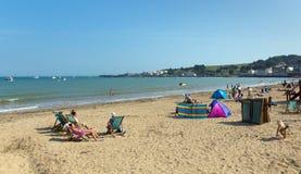 Koppla av på den Swanage stranden Dorset England UK med solstolar Arkivfoto