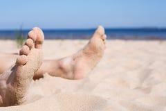 Koppla av på en öde strand - solbada royaltyfri fotografi