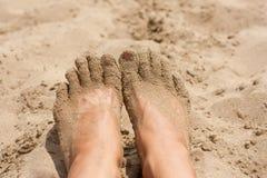 Koppla av på en strand, fot för ung kvinna i den varma sanden Royaltyfri Bild