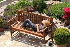 Koppla av på en trädgårds- bänk royaltyfri foto