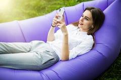 Koppla av på ny luft Den nätta unga kvinnan som ligger på den uppblåsbara mobiltelefonen för soffalamzacbruk, medan vila på gräs, royaltyfri foto