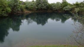 Koppla av sikt av den härliga albanska naturen Ljust regn faller i en naturlig sjö som omges av grön flora arkivfilmer