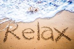 Koppla av skriftligt in i sanden på en strand Arkivbild