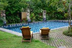 Koppla av stolar med simbassängen i Bali, Indonesien Arkivfoto