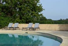Koppla av stolar nära simbassängen Arkivfoton