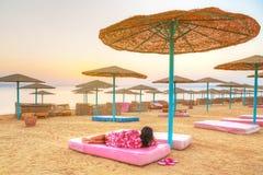 Koppla av under slags solskydd på stranden av Röda havet Arkivbilder
