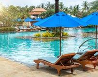 Koppla av vid pölen i lyxigt hotell på ön av Thailand Par av trästol under paraplyet Royaltyfria Bilder