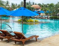 Koppla av vid pölen i lyxigt hotell på ön av Thailand Par av trästol under paraplyet Royaltyfri Bild