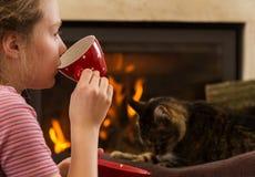 Koppla av vid spisen med drinken och katten royaltyfri fotografi