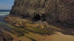 Koppla ihop anseendet på den lösa stranden med klippor bakom, Portugal arkivfilmer