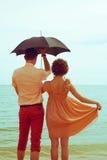 Koppla ihop anseendet på near vatten för stranden under paraplyet Royaltyfri Bild