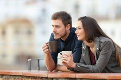 Koppla ihop att koppla av dricka kaffe i en balkong på semester royaltyfri foto
