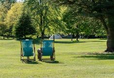 Koppla ihop att koppla av itu deckchairs på typisk engelsk gräsmatta Royaltyfria Bilder