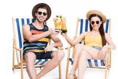 koppla ihop att koppla av på strandstolar och att klirra exponeringsglas med coctailar, royaltyfri foto