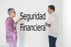 Koppla ihop att diskutera finansiell säkerhet mot den vita väggen med spansk text Seguridad Financiera Royaltyfri Bild