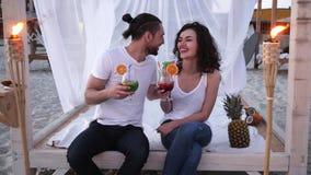 Koppla ihop att dricka den kulöra coctailen sätter på land på en exotisk semester, cocktailpartyet, bungalow på stranden, tropisk arkivfilmer