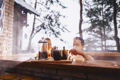 Koppla ihop att dricka varmt te, medan sitta i den varma vinteryttersidan arkivbilder