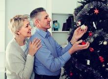 Koppla ihop att förbereda sig att fira i hans hem- jul och nya år Royaltyfria Bilder