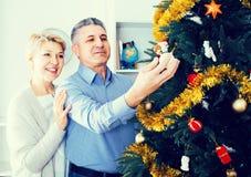 Koppla ihop att förbereda sig att fira i hans hem- jul och nya år Arkivbilder