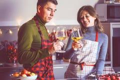 Koppla ihop att fira jul i kök- och drinkvinet arkivbild