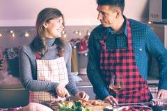 Koppla ihop att fira jul i köket som lagar mat jul, duckar eller gåsen royaltyfri fotografi