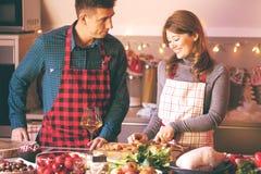 Koppla ihop att fira jul i köket som lagar mat jul, duckar eller gåsen royaltyfri foto