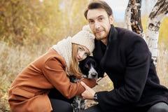 Koppla ihop att gå med hunden i parkera och att krama Hösten går män Arkivfoton