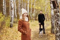 Koppla ihop att gå med hunden i parkera och att krama Hösten går män Royaltyfri Bild