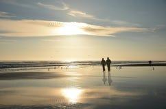 Koppla ihop att gå på den härliga dimmiga stranden på soluppgång Royaltyfria Bilder