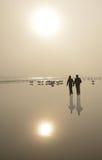 Koppla ihop att gå på den härliga dimmiga stranden på soluppgång Arkivbild