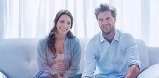 Koppla ihop att göra deras räkenskap som sitts i en soffa arkivfoton