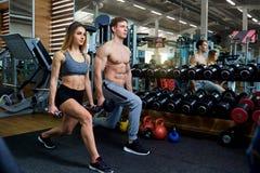 Koppla ihop att göra satta sitta-UPS med hantlar i idrottshallen royaltyfri foto
