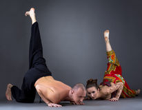 Koppla ihop att göra yoga i studio, på grå bakgrund Arkivfoton