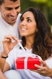 Koppla ihop att ge gåva på födelsedag- eller årsdagberöm Royaltyfri Bild