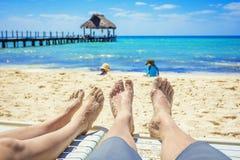 Koppla ihop att hålla ögonen på deras ungar att spela på stranden på semester Arkivbilder