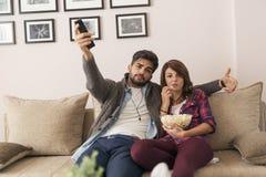 Koppla ihop att hålla ögonen på en lek på TV och att äta popcorn royaltyfri foto