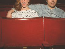 Koppla ihop att hålla ögonen på en spännande film i en filmbiograf Royaltyfri Foto