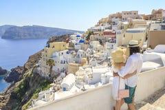Koppla ihop att hålla ögonen på sikten av cityscape av den Oia byn i Santorini arkivfoton