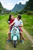 Koppla ihop att ha gyckel på mopeden runt om risfält i Kina fotografering för bildbyråer