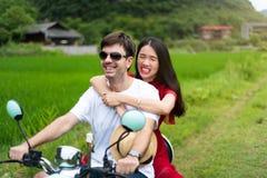 Koppla ihop att ha gyckel på mopeden runt om risfält i Kina royaltyfri bild