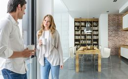 Koppla ihop att ha kaffe i ett modernt hus arkivbild