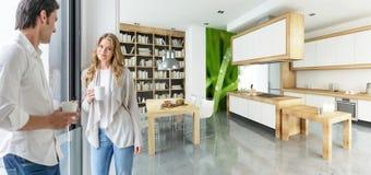 Koppla ihop att ha kaffe i ett modernt hus royaltyfri bild