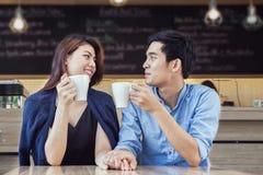 Koppla ihop att ha kaffe och rym handen förälskad tillsammans i kafé Fotografering för Bildbyråer
